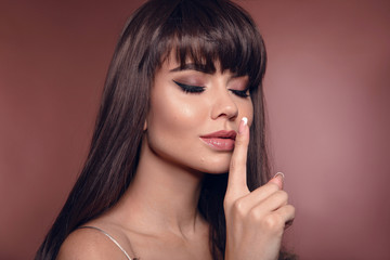 Beauty portrait of brunette woman with eyeliner makeup and long healthy shiny hair style isolated on brown posing in studio. Finger showing hush silence sign.