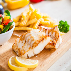 Fish dish - fried fish fillet with vegetables and french fries