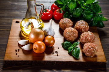 Raw meatballs on cutting board on wooden background