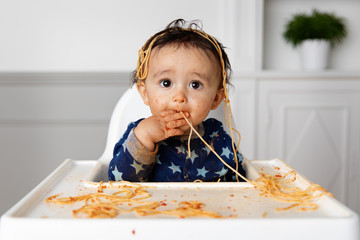Funny baby in high chair eating spaghetti with his hands