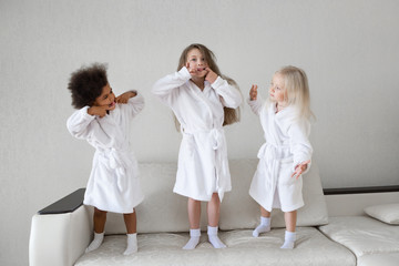 Girls indulge stick out tongue. Little girls in white coats playing make funny faces grimaces facial expressions.