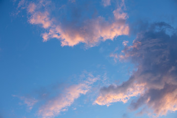 Sunset clouds with a pink contour on the blue sky