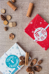 Christmas composition. Christmas red and white gifts boxes and cinnamon sticks on canvas background. Flat lay