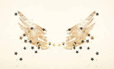 Golden glitter and glittering stars on abstract watercolor wings in vintage nostalgic colors.