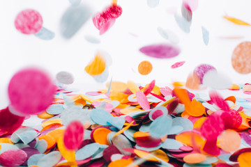 Multicolored round confetti is flying to the table. Festive concept. Selective focus