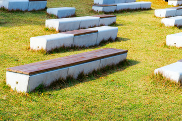 Concrete with wooden top bench in the park on green grass