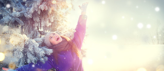 Christmas scene. Winter joyful beauty girl  having fun outdoors in winter park under decorated Christmas tree. Beautiful young woman celebrating Xmas and New Year