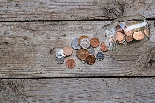 Uk money spilling out of jar