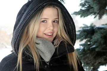 Девушка зимой возле сосны.