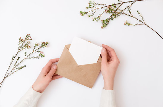 Woman's hands holding kraft envelope with blank wedding invitation card. Creative mock up layout on white background, top view, flat lay, overhead. Minimalistic woman's desk, flowers, greeting card.