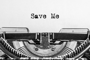 Save me, typed text on a vintage typewriter. Black ink on old paper, call for help, SOS.