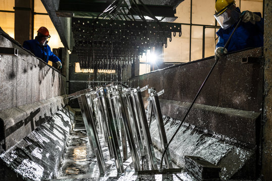 People at work galvanizing metallic structures in a zinc bath