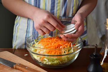 Woman cook sauerkraut or salad on wooden background. Step 3 - Salt the cabbage. Fermented preserved vegetables food concept.