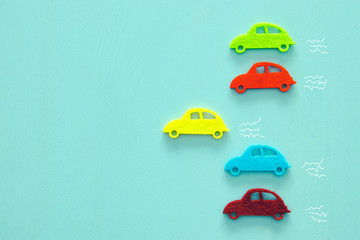 Abstract pastel colored wooden background with vibrant car shapes.