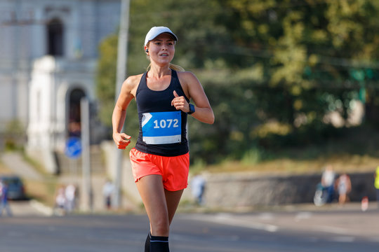 Young sporty woman running in marathon competition