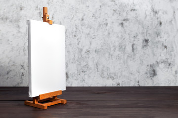 White blank synthetic canvas stretched on subframe and an easel standing on a brown wooden table