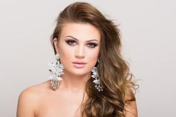 Portrait of beautiful young woman in makeup wearing big earrings. Closeup, no retouch, studio lighting.