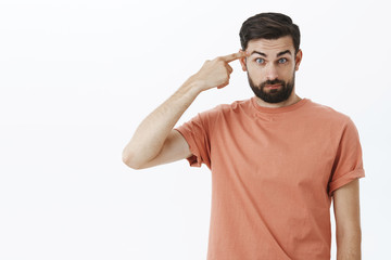 Are you out of mind. Portrait of angry and shocked bearded dark-haired 30s man raising eyebrows shook and stunned rolling index finger on temple as blaming friend making stupid, crazy action