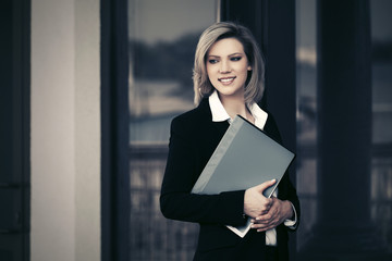 Happy young business woman with a file folder at office building