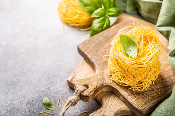 Fresh egg pasta tagliatelle nest on wooden cutting board with basil leaf. Healthy italian food concept with copy space.