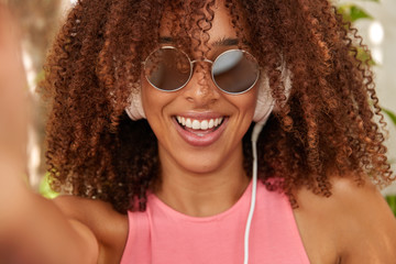 Fashionable black lady with Afro haircut, being real meloman, listens songs from playlist, has trendy white headphones, makes selfie portrait, wears shades, smiles positively. Close up shot.