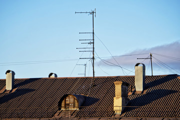 Old analog television antennas of meter and decimeter ranges on the roof of an old five-story house