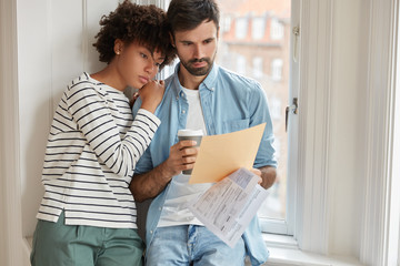 Mixed race family couple study budget together, look attentively at documentation, drink takeaway coffee, stand near window in flat. Administratve managers check financial documents, cooperate