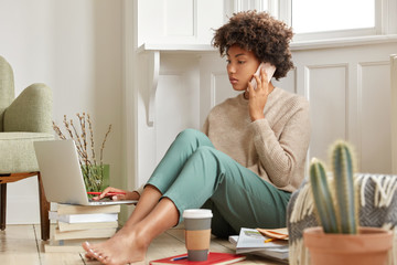 Photo of busy hard working college student has telephone consultancy, focused into portable laptop computer which stands on pile of books, poses barefoot at floor, disposable cup of coffee near