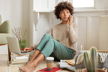 Photo of black woman has telephone conversation, discusses main issues, holds modern cell phone, work with laptop computer, drinks takeaway coffee, reads books, makes course paper, dressed casually