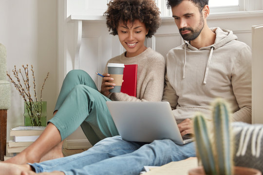 Image of family couple choose items for home in internet web store, make shopping online together, look at screen of laptop, drink espresso, sit on floor together. Technology and leisure concept