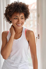 Vertical shot of pleasant looking Afro American woman with thoughtful expression, has pleasant smile, dressed in white vest, poses near window, has spare time at home. People and lifestyle concept