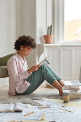Vertical shot of serious black lady dressed in fashionable shirt and trousers, has attentive gaze in textbook, surrounded with many papers, works at portable notebook, connected to wireless internet