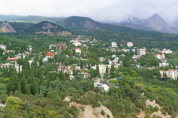 A large black cloud is coming from the mountains to the low-rise resort village Simeiz