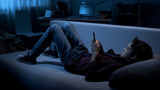 Teenager chatting with friends on smartphone lying on couch, social network
