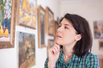 Portrait of a young woman looking at a painting in an art gallery or museum.