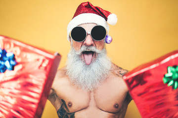 Tattooed fit santa claus doing crazy and giving christmas gifts - Trendy beard hipster senior wearing xmas clothes and holding presents - x-mas Celebration and holidays concept