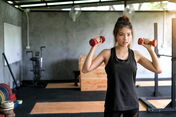 Beautiful young asian woman lifting dumbbell at gym