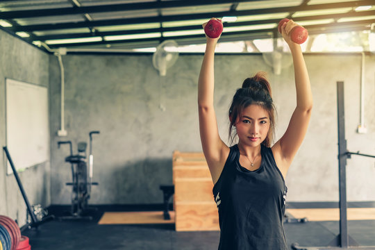 Beautiful young asian woman lifting dumbbell at gym