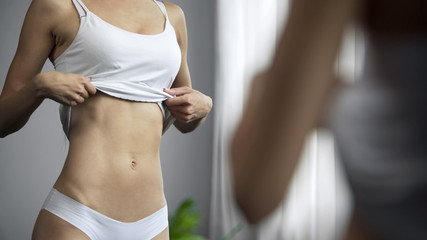Dissatisfied woman standing in front of mirror, looking at her slim body, diet