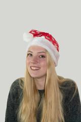 lachendes, Junges Mädchen mit langen blonden Haaren und Weihnachtsmütze.