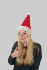 lachendes, Junges Mädchen mit langen blonden Haaren und Weihnachtsmütze zeigt den Daumen nach oben.