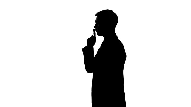 Silhouette of person showing gesture of silence, censorship, confidential data