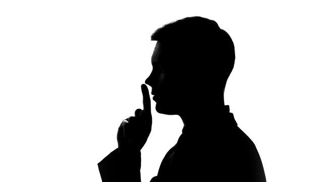Man showing gesture of silence, non disclosure of secret data, fingers on lips