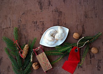Merry Christmas and Happy New Year holidays, festive background with fir branches, shortbread with walnuts, whole walnuts and Christmas decorations. Top view