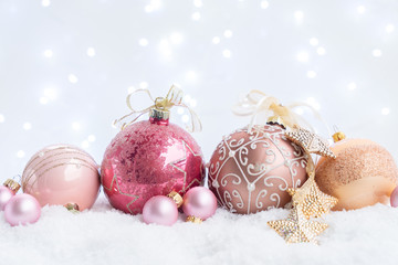 White christmas with snow - pink and golden ball decorations close up with bokeh lights in background