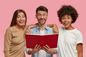 Indoor shot of cheerful handsome man and his two sisters embrace and stand closely, read book, have happy expression, like learning something new, isolated over pink background. Teamwork concept