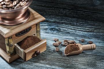 Coffee grinder scoop grains on wooden board