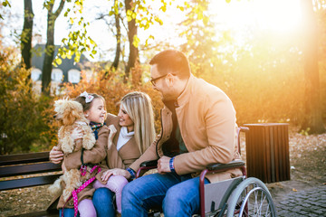 Disabled father in wheelchair enjoying with his daughter, wife and dog outdoors in park.