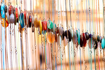 Abstract background. Samples of colorful women's jewelry on a chain of artificial stone on bokeh background. Cropped shot, close-up, vertical, blurred. Concept of beauty.