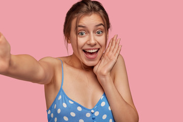Photo of amazed cheerful young woman with happy overjoyed expression, keeps hand near cheek, dressed in polka dot dress, poses against pink background. Content emotive European girl poses indoor